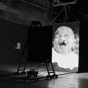 Monique Bertrand, Un Devoir d'effroi, 2001-2002. Acier, épreuves argentiques, ruban adhésif, aluminium, câble électrique,12 ampoules photographiques 150 watts. 345 x 180 x 560 cm. Photo : Dominique Malaterre.