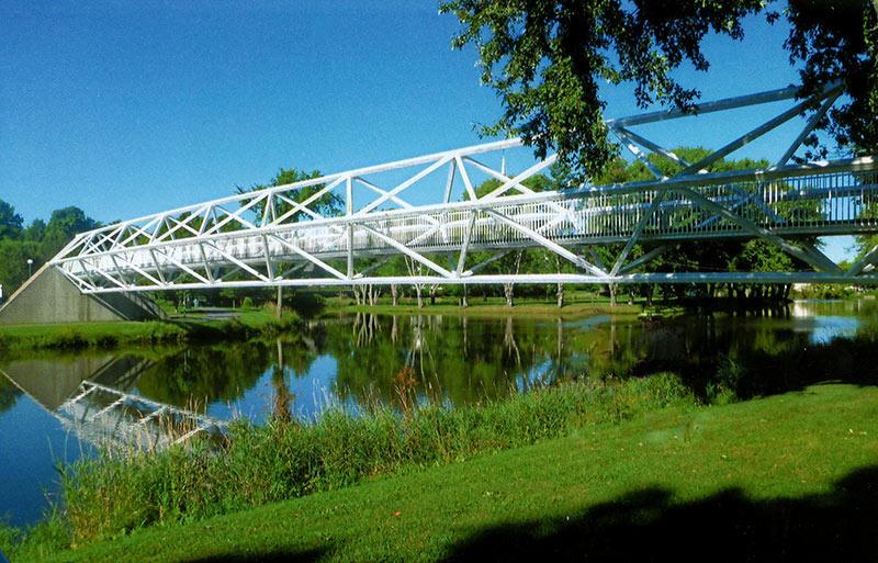 Armand Vaillancourt, Passerelle Vaillancourt,  1990. Acier, béton, bois. 609 x 609 x 6094 cm. Pont piétonnier sur la rivière Bourbon, Plessisville. Photo avec l'aimable autorisation de l'artiste.