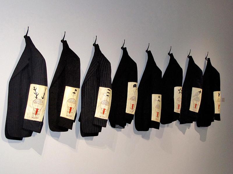 Michel Lagacé, Les plâtrés, 2012. Vestons en tissus, crochets de métal, acrylique et encre sur le tissus des vestons. 90 x 460 cm. Photo avec l'aimable autorisation de l'artiste.